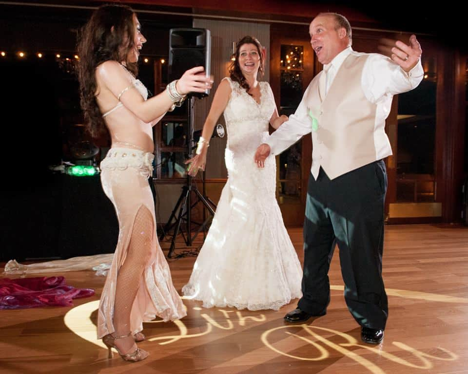 Carrara Nour, a belly dancer in Orlando, dances with the newlyweds at their Lake Mary, FL wedding at Timacuan Country Club